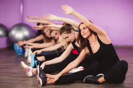 Portrait of fitness class and instructor doing stretching exercise on yoga mats. Group of people in a gym doing aerobics or warming up with gymnastics and stretching exercises photo