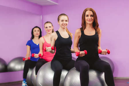 Group of fit people at the gym exercising. fitness, sport, training and lifestyle concept - group of smiling women with exercise balls in gym. Group of people engaged in fitness club photo