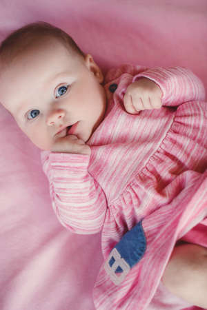 Little baby girl with short hair and blue eyes, wearing a pink dress, lying in his bed at home on a pink blanket, carefully looking at the camera and holding a finger in the mouth. photo