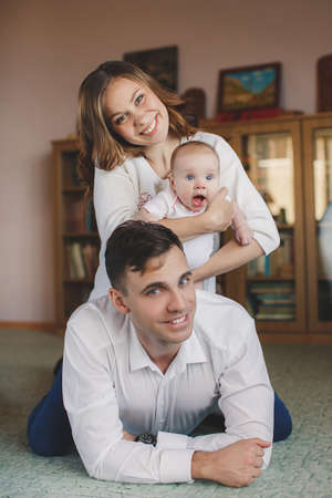gray eyes: Young couple, man, brunette with gray eyes, dressed in a white shirt and blue jeans, a woman with a curvy brunette with beautiful hair and gray eyes and blue jeans, the mother is holding her daughter-blue-eyed girl in a pink dress and pink tights.