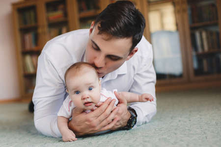 gray eyes: Young handsome man, brunette with short hair, dressed in a white shirt and blue jeans is holding her little daughter, a girl with gray eyes, dressed in a white shirt and white socks, the girl looks at the photographer.