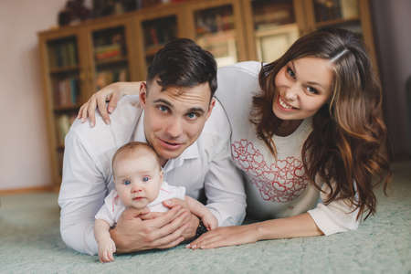 Young couple, man, brunette with gray eyes, dressed in a white shirt and blue jeans, a woman with a curvy brunette with beautiful hair and gray eyes and blue jeans, the mother is holding her daughter-blue-eyed girl in a pink dress and pink tights. photo