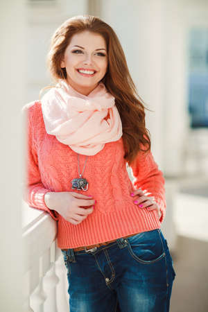 Portrait of a beautiful young woman with long hair chestnut, hazel eyes and light make-up, wearing a pink knitted sweater and a pink scarf around his neck, a beautiful smile and straight white teeth, posing for a photograph near the white building.