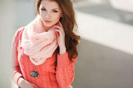 hazel eyes: Retrato de una hermosa mujer joven con el pelo casta�o largo, ojos color avellana y la luz de maquillaje, vestido con una rosa de punto su�ter y una bufanda rosada alrededor de su cuello, una hermosa sonrisa y dientes blancos, posando para una fotograf�a cerca del edificio blanco.