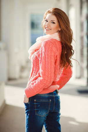 eyes hazel: Portrait of a beautiful young woman with long hair chestnut, hazel eyes and light make-up, wearing a pink knitted sweater and a pink scarf around his neck, a beautiful smile and straight white teeth, posing for a photograph near the white building.