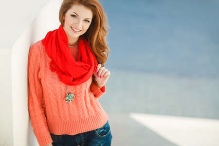 Portret van een mooie jonge vrouw met lang haar kastanje, bruine ogen en lichte make-up, het dragen van een roze gebreide jas en rode sjaal om zijn nek, een mooie glimlach en rechte witte tanden, poseren voor een foto in de buurt van het witte gebouw.