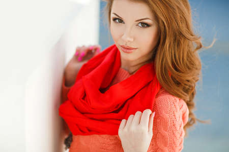 hazel eyes: Portrait of a beautiful young woman with long hair chestnut, hazel eyes and light make-up, wearing a pink knitted jacket and red scarf around his neck, a beautiful smile and straight white teeth, posing for a photograph near the white building.
