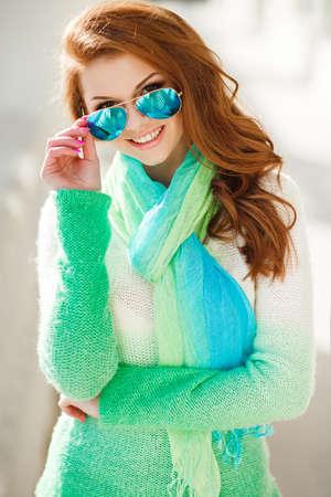 hazel eyes: Retrato de una hermosa mujer joven con el pelo casta�o largo, ojos color avellana y la luz de maquillaje, vestida de blanco y verde su�ter de punto y una bufanda alrededor de su cuello, una hermosa sonrisa y dientes blancos, posando para una fotograf�a junto al edificio blanco Foto de archivo