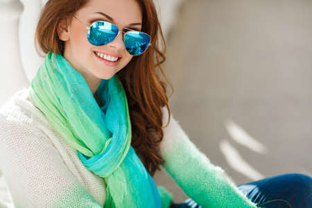 eyes hazel: Portrait of a beautiful young woman with long hair chestnut,hazel eyes and light make-up,dressed in white and green knit sweater and a scarf around his neck, a beautiful smile and straight white teeth,posing for a photograph near the white building Stock Photo