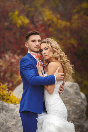 The bride and groom - the photograph in the Park. Groom - a young dark-haired man in a blue suit and pink wedding tie - butterfly and blue-eyed bride - curly blond with long hair and a white wedding dress, posing, hugging in the park. photo