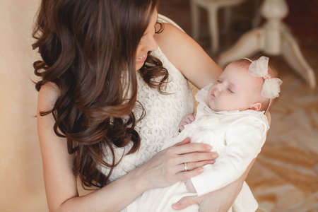Mother holding head of her newborn son in hands. The baby on hands at mum. Loving mother hand holding cute sleeping newborn baby child photo