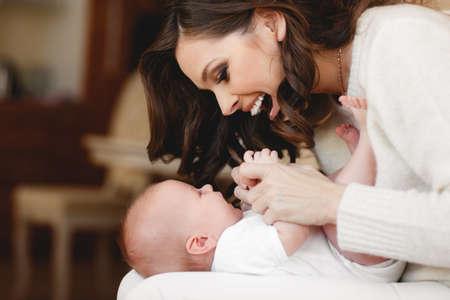 母の手で彼女の生まれたばかりの息子の頭を保持します。母の手に赤ちゃん。愛情のある母手かわいい寝ている生まれたばかりの赤ちゃん子供 写真素材