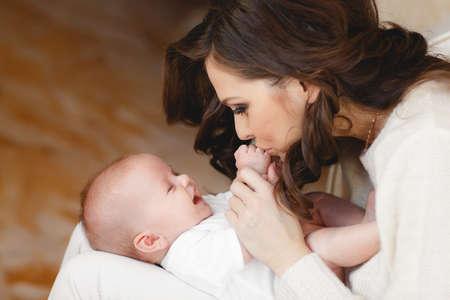 Moeder houdt het hoofd van haar pasgeboren zoon in handen. De baby op handen bij mum. Liefhebbende moeder de hand houden schattige slapende pasgeboren baby kind