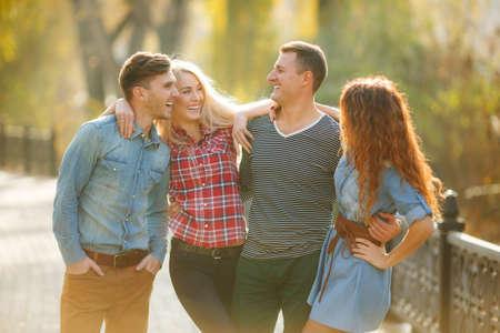 cuatro amigos, dos mujeres y dos hombres relajarse y divertirse en el parque de otoño, niña, de pelo largo rubio y morena en un vestido de mezclilla azul, la otra en una camisa a cuadros de color rojo, los hombres -tanto morenas en una camisa de mezclilla azul, la otra en una camiseta. Foto de archivo