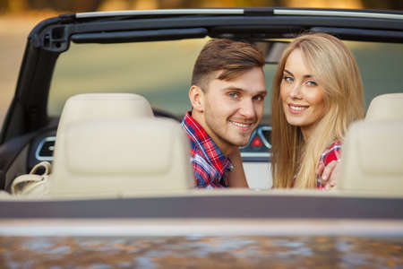 Young hip couple - man and woman - with cabriolet convertible car in summer on a day trip. Couple driving convertible car enjoying a summer day photo
