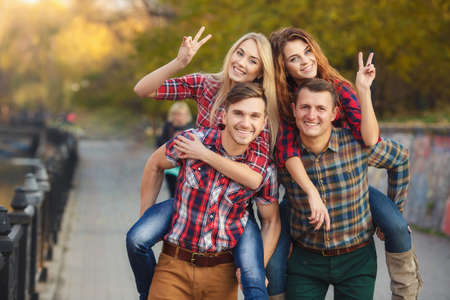 four friends, two women and two men relax and have fun in autumn park, girl, long-haired blonde and brunette in a blue denim dress, the other in a red plaid shirt, men-both brunettes in a blue denim shirt, the other in a T-shirt. photo