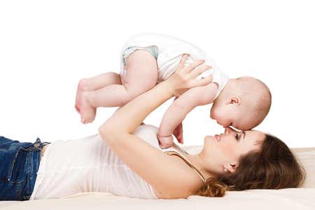 kinderen: Portret van moeder en kind spelen op het bed in de slaapkamer, geïsoleerd op een witte achtergrond op een lichte beige deken baby met pluizige kort haar, gekleed in een wit T-shirt, Moeder brunette met lang krullend haar en grijze ogen, gekleed in een wit overhemd