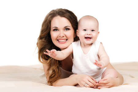 Portrait of a mother and baby isolated on white background on a light beige blanket,brown-eyed baby with a fluffy short hair,in a white t-shirt and the mother is a brunette with long curly hair and grey eyes,wearing a white t-shirt,smiling and posing