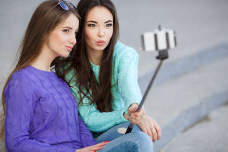 stick people: young beautiful friends students taking selfie stick picture together in town happy on sunny day. Closeup of two cheerful friends having fun and taking photos of themselves on smart phone.