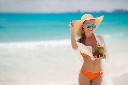cocotier: Une femme avec une belle figure, brune aux longs cheveux raides en bikini orange, dans un grand chapeau de paille avec une �charpe blanche transparente � la lumi�re drap� derri�re des lunettes noires debout sur une plage, de boire avec une paille lait de noix de coco.