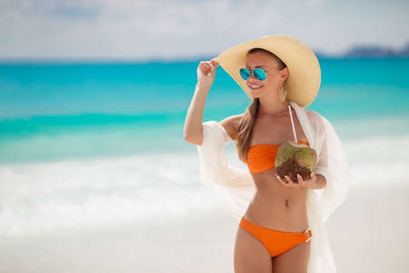 A woman with a beautiful figure, brunette with long straight hair in orange bikini, in a large straw hat with a light transparent white scarf draped behind dark glasses standing on a beach, drinking through a straw coconut milk. photo