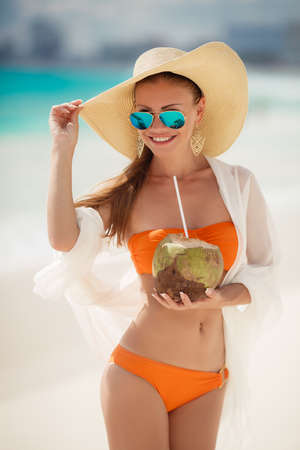 A woman with a beautiful figure, brunette with long straight hair in orange bikini, in a large straw hat with a light transparent white scarf draped behind dark glasses standing on a beach, drinking through a straw coconut milk.