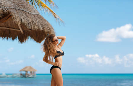 hot breast: Красивая молодая женщина брюнетка с длинными прямыми волосами в черном бикини, носить солнцезащитные очки на тропический курорт, стоящая под пальмой позируют для фотографии на тропическом пляже.