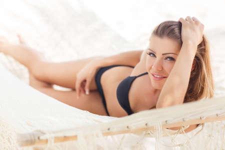 hamaca: Modelo, una mujer joven, una morena de ojos gris-verdes y el pelo largo y liso, un bikini de color negro, disfrutar del sol y el calor, acostado en el color beige claro hamaca en el resort tropical.