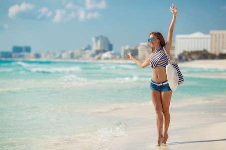 Een mooie jonge vrouw, een brunette met lang steil haar, in blauwe korte broek, het dragen van een zonnebril met blauwe glazen, gestreepte strandtas en een gestreept t-shirt, staande in de buurt van de oceaan genieten van de vakantie op een tropisch resort. Stockfoto