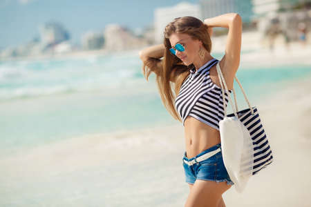 A beautiful young woman,a brunette with long straight hair,in blue shorts, wearing sun glasses with blue glasses, striped beach bag and a striped t-shirt,standing near the ocean enjoying the vacation on a tropical resort. Zdjęcie Seryjne