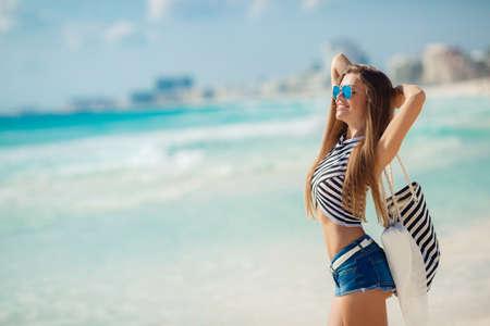美しい若い女性が、長いストレートの髪、青い半ズボンでブルネット トロピカル リゾートで休暇を楽しむ、海のそばに立っているの縞模様の t シャ