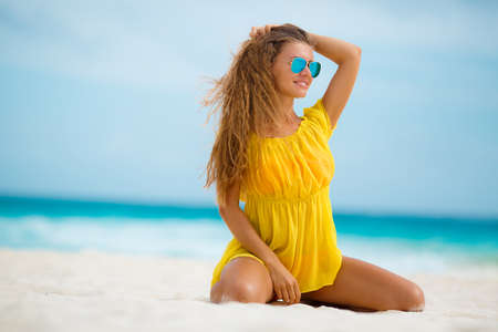 transparent dress: Young, slender,beautiful woman,brunette,long straight hair, sunglasses with blue mirror glasses,wearing a yellow short transparent dress,enjoying the holidays,spending time on the sandy shores of the blue ocean. Stock Photo