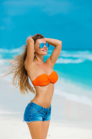 Young, slender,beautiful woman,brunette,long straight hair, sunglasses with blue mirror glasses,dressed in blue shorts and an orange bra,enjoying the holidays,spending time on the sandy shores of the blue ocean. photo