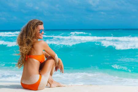 若い、細い、美しい女性、ブルネット、長いストレートの髪、青いミラーのメガネ、サングラスを包んだオレンジ色のビキニ青い海の砂浜で時間を