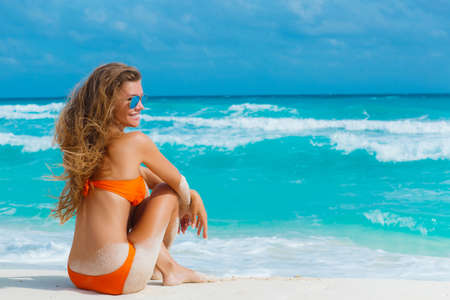 Young, slender,beautiful woman,brunette,long straight hair, sunglasses with blue mirror glasses,dressed in an orange bikini,enjoying the holidays,spending time on the sandy shores of the blue ocean.