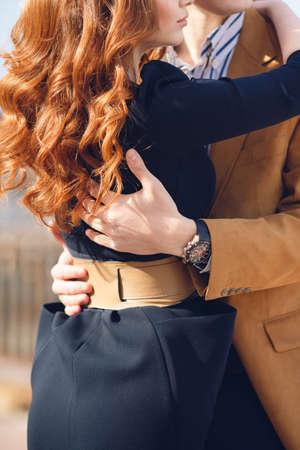 pasion: Una pareja joven, con estilo en el amor, una mujer con un vestido de color oscuro corto y un hombre en una chaqueta de color marr�n claro y blanco en una camisa a rayas oscuro, de pie junto a la otra en una calle de la ciudad, un abrazo y mira en la misma direcci�n