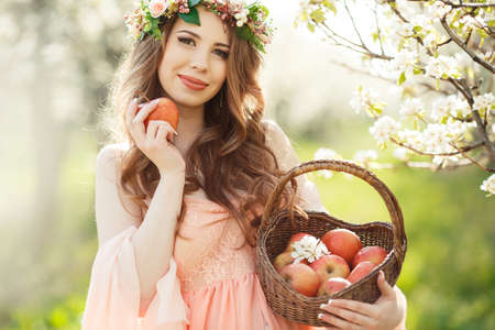 Young beautiful pregnant womanbrunette with long curly hairwears on his head a wreath of flowersdressed in a long gown of pinkholding a basket with red applesspends time alone in a spring flower garden. photo
