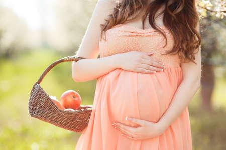 Junge schöne schwangere womanbrunette mit langen lockigen hairwears auf dem Kopf einen Kranz von in einem langen Kleid aus pinkholding einen Korb mit roten applesspends Zeit allein in einer Frühlingsblumengarten flowersdressed.