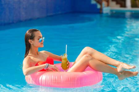 맑은 물이 내부 튜브 거짓말과 재미를 함께 수영장에서 여름에 포즈 젊은 예쁜 패션 여자 몸. 잘 나는 건강한 라이프 스타일을 생각합니다
