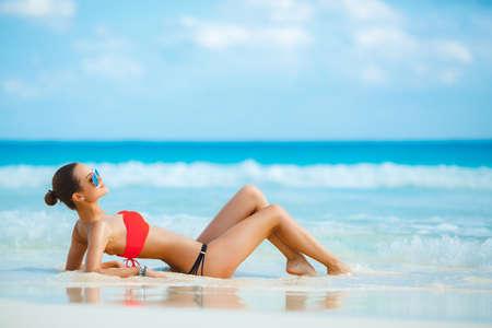 mujer sexy: Chica atractiva y sexy en la playa. Hembra joven disfrutando de un d�a soleado en la playa tropical. Hermosa chica tomando el sol bajo el sol de verano tumbado en la arena en la playa con agua azul