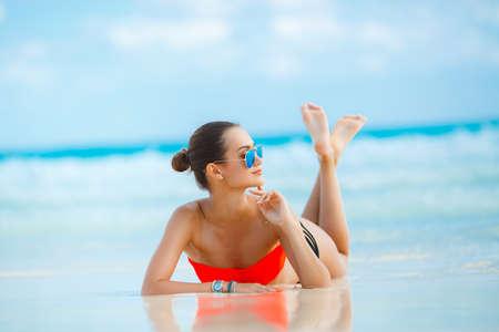 Aantrekkelijk en sexy meisje op het strand. Jonge vrouwelijke genieten van zonnige dag op het tropische strand. Mooi meisje zonnen onder de zomerzon liggen in zand op het strand met blauwe water