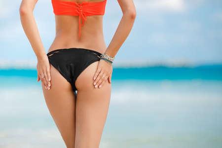 nude butt: Sexy sandy woman buttocks on tropical beach background near ocean. close up outdoor shot of young woman in white bikini sunbathing at sea shore. Black bikini