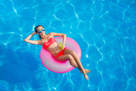 tubes: Young pretty fashion woman body posing in summer in pool with clear water lying inner tube and having fun. Well I am healthy lifestyle