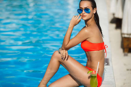 cocktail drinks: Tenned beautiful woman in orange bikini and sunlasses sitting in swimming pool with cocktail. Fashionable portrait. Elegant woman in a bikini and sunglasses Stock Photo