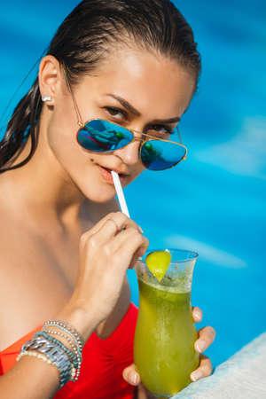 Tenned beautiful woman in orange bikini and sunlasses sitting in swimming pool with cocktail. Fashionable portrait. Elegant woman in a bikini and sunglasses photo