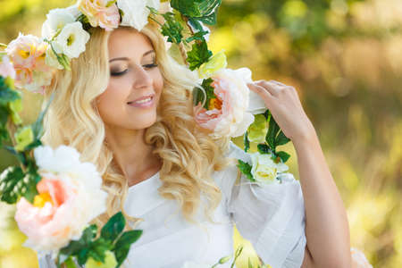 Blueeyed bride with a beautiful blond curlylong hair in a white wedding dress and a beautiful wreath of pink and white rosesswinging on a swing decorated with flowers rose in the summer outdoors in the Park. photo