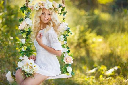 Blue eyed Braut mit einem schönen blonden lockigen langen Haaren in einem weißen Hochzeitskleid und einem schönen Kranz aus rosa und weißen Rosen schwingt auf einer Schaukel mit Blumen geschmückt