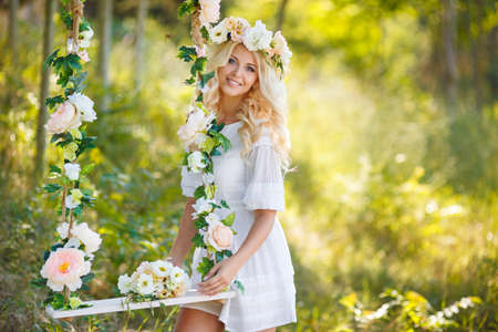 Blueeyed bride with a beautiful blond curlylong hair in a white wedding dress and a beautiful wreath of pink and white rosesswinging on a swing decorated with flowers rose in the summer outdoors in the Park. Foto de archivo