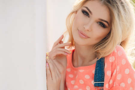 Summer portrait of a beautiful woman. Very beautiful blonde girl with big brown eyes bushy long hair dressed in a pink Tshirt with white polka dots and denim overalls in dark blue green park resting in a sunny summer day Standard-Bild