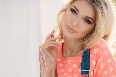 mooie vrouwen: Zomer portret van een mooie vrouw. Zeer mooie blonde meisje met grote bruine ogen bossige lang haar, gekleed in een roze shirt met witte stippen en denim overalls in donkerblauw groen park rust op een zonnige zomerdag Stockfoto